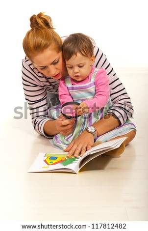 Mother with girl reading book  home and  holding magnifier - stock photo
