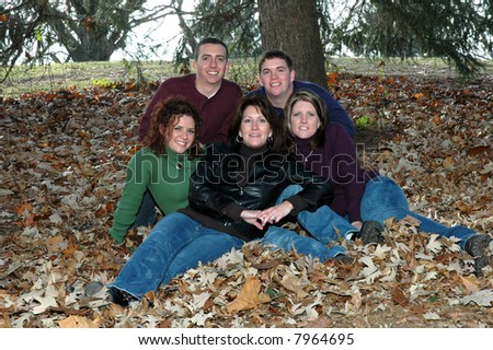 mother with grown children in leaves - stock photo