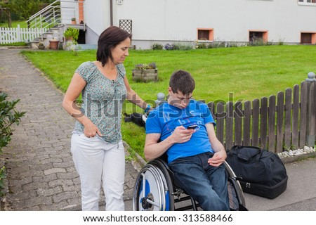 Mother with handicapped son waiting for the school bus - stock photo