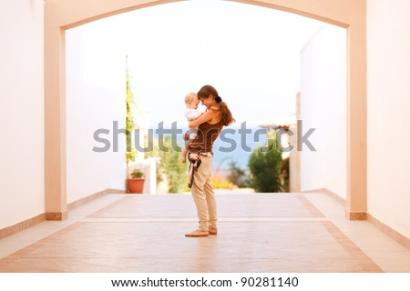 Mother with happy baby playing on street - stock photo
