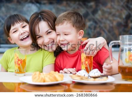 Mother with happy children drink juice - stock photo