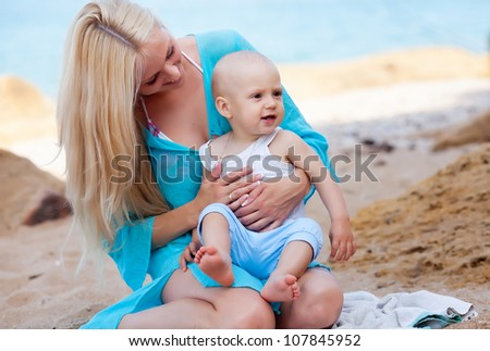 Mother with her baby playing on the beach - stock photo