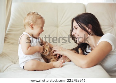 Mother with her baby playing with pet on a sofa at living room - stock photo