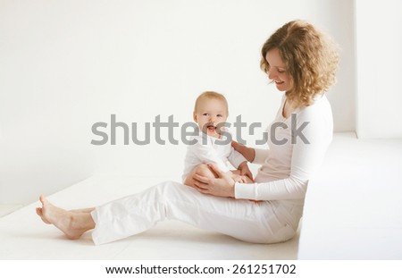 Mother with her baby together at home in white room - stock photo