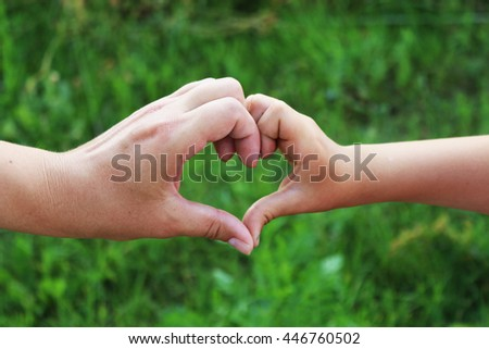 Mother with her child made a heart with your hands - stock photo