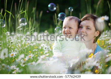 Mother with her child playing in camomile field - stock photo