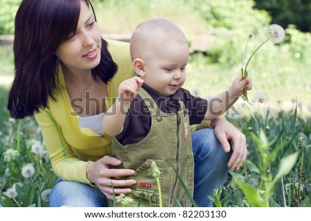 Mother with her child playing in dandelion field - stock photo