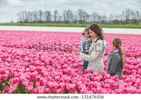 Mother with her child walks between of the purple tulips field - stock photo