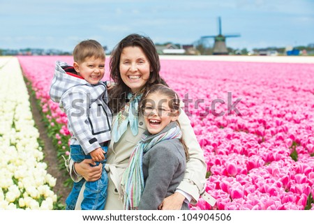 Mother with her child walks between of the white and purple tulips field