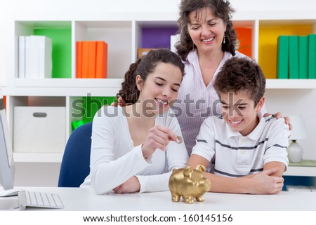 mother with her children putting money in piggybank, family saving  - stock photo