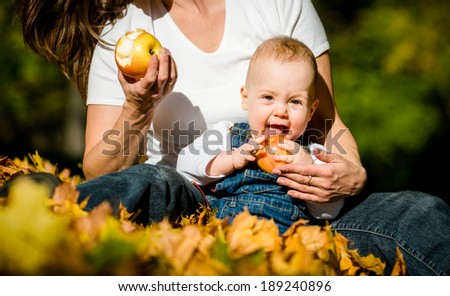 Mother with her cute baby eating apples outdoor in autumn nature - stock photo
