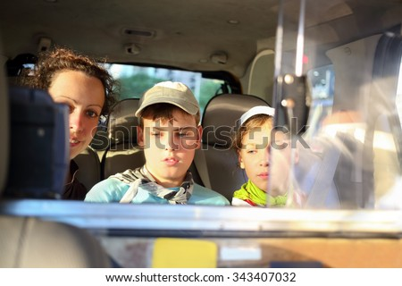 mother with her daughter and son in the backseat of a taxi - stock photo