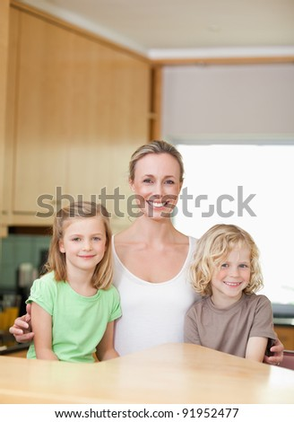Mother with her daughter and son in the kitchen together - stock photo