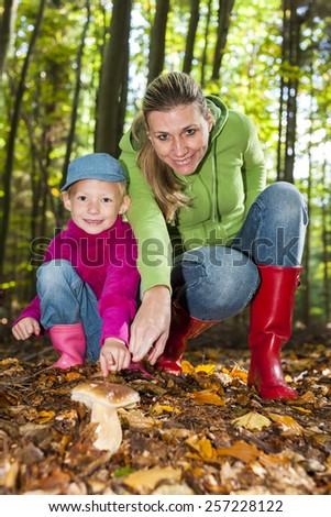 mother with her daughter doing mushroom picking - stock photo