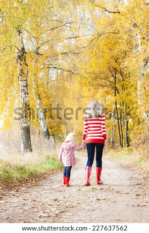 mother with her daughter in autumnal alley - stock photo