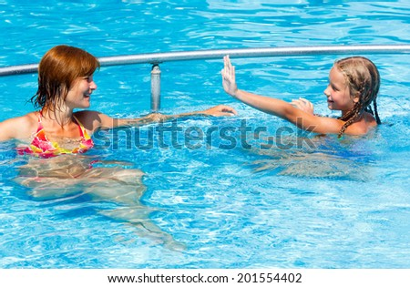 Mother with her daughter in the summer outdoor pool.