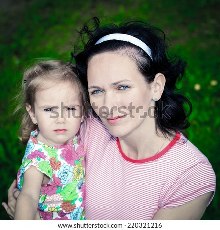 Mother with her daughter looking at the camera. Delicate and sweet portrait of a mum and daughter - stock photo
