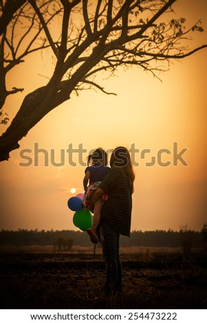 Mother with her daughter looking sunset - stock photo