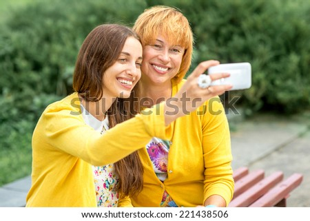 Mother with her daughter taking selfie picture in the park - stock photo