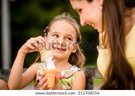 Mother with her daughter tasting together icecream outdoor in park - stock photo