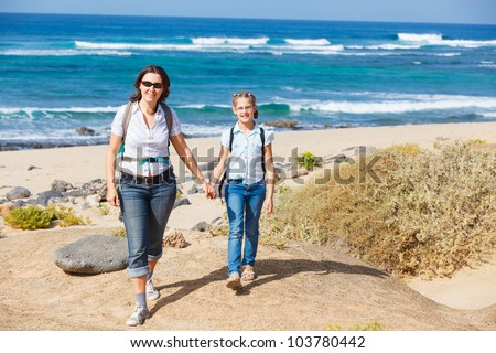 Mother with her daughter walking on a beach, wearing jeans and white shirts - stock photo