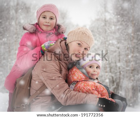 Mother with her daughters in the winter. - stock photo