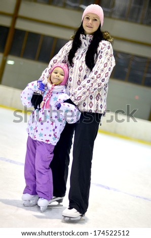 Mother with her daughters skates on ice skating - stock photo