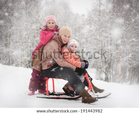 Mother with her daughters with a sled in the winter.