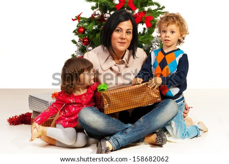 Mother with her kids sitting near Christmas tree - stock photo