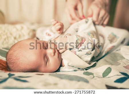 Mother with her newborn baby care hands at home - stock photo