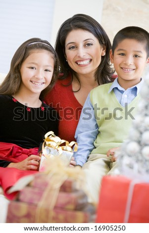 Mother With Her Son And Daughter Holding Christmas Gifts - stock photo