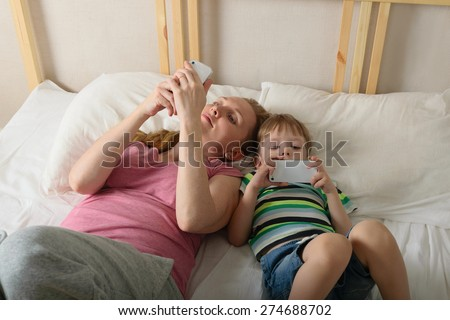 Mother with her son lying on the bed with the phone in his hand. - stock photo