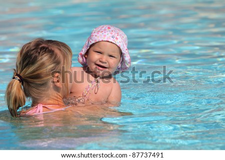Mother with her toddler daughter in a swimming pool - stock photo