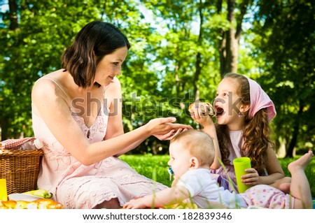 Mother with her two children having picnic and eating in park - stock photo