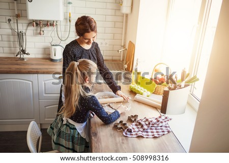 Mother with her 6 years old kid cooking cookies in the kitchen, casual ...