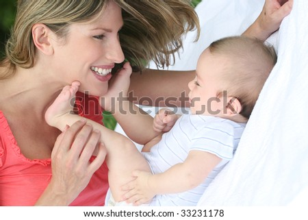 Mother with infant baby boy son, smiling and happy - stock photo
