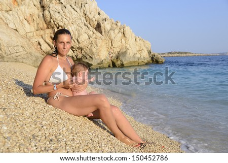 Mother with infant-daughter on the beach - stock photo