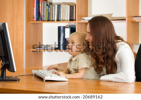 Mother with kid looking computer monitor in office - stock photo