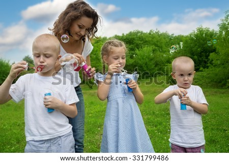 Mother with kids blowing bubbles in park - stock photo