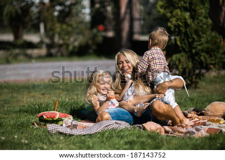 Mother with kids in the garden - stock photo
