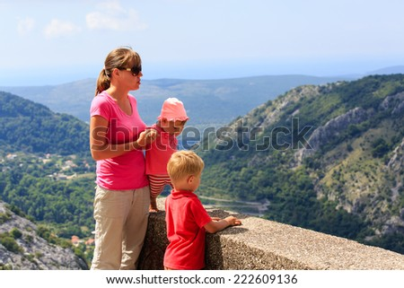 mother with kids looking at scenic view in mountains vacation