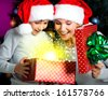 Mother with little child opens the box with gifts on the christmas holiday - indoors - stock photo