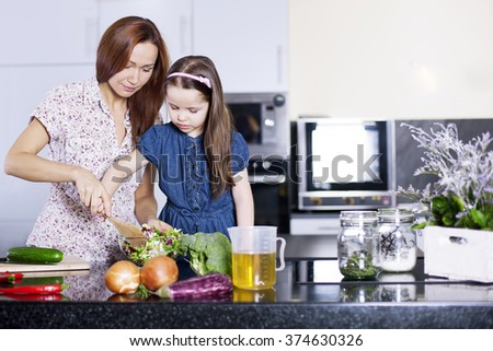 Mother with little daughter cooking in the 