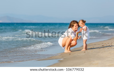 Mother with little daughter on the beach - stock photo