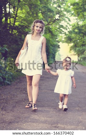 mother with little daughter walking in the forest and holding hands - stock photo