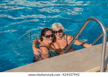 Mother with love hugs her daughter in water at the Edge of a Swimming Pool. - stock photo