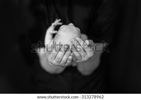 Mother with newborn baby at home, black background