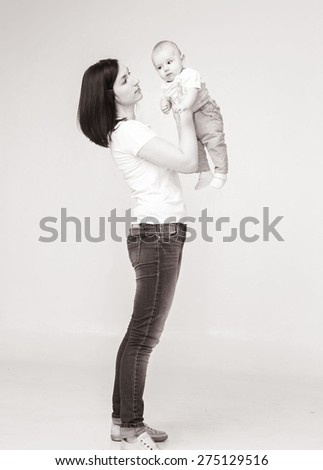 Mother with newborn baby black and white full length portrait - stock photo