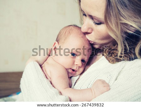 Mother with newborn baby child family home - stock photo