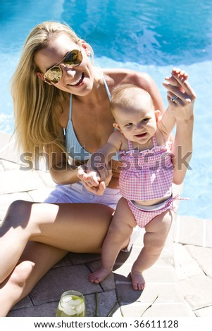 Mother with six month old baby next to a swimming pool - stock photo